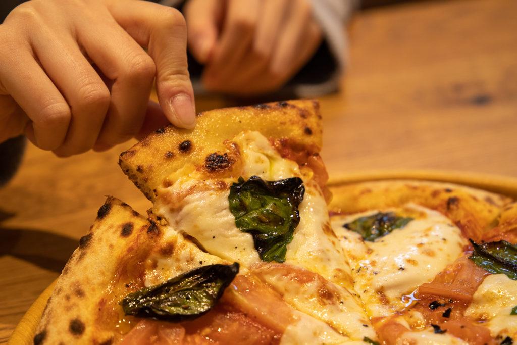茅ヶ崎おすすめピザ_ナポリの窯茅ヶ崎店商品_トマト多めのマルゲリータを手に取る