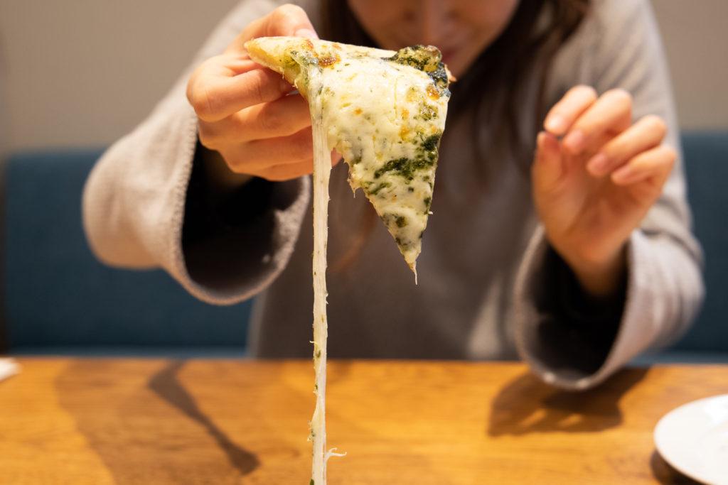 茅ヶ崎おすすめピザ_ナポリの窯茅ヶ崎店商品_バジルとモッツァレラチーズを手に取る